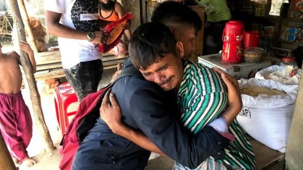 Ahmed Ullah hugs a man inside a refugee camp in Bangladesh.