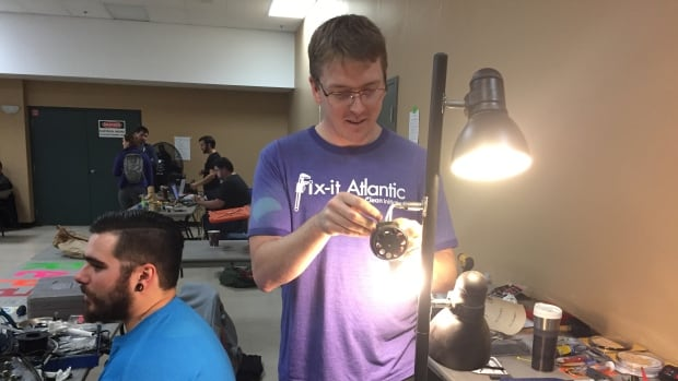 Aaron Taylor fixes a 40-year-old lamp brought to the fair on Saturday.