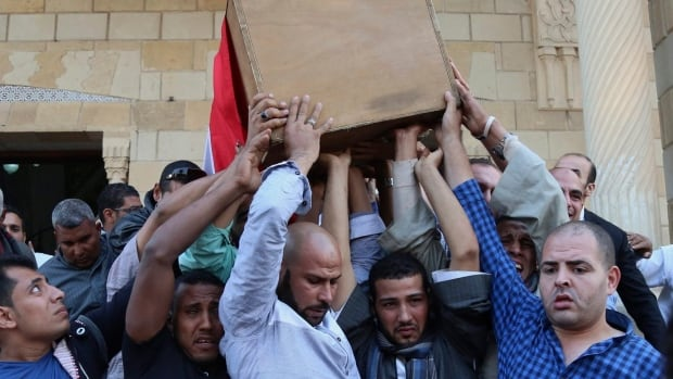 People carry the coffin Saturday of police captain Ahmed Fayez, who was killed in a gun battle which began Friday in al-Wahat al-Bahriya area in Giza province, about 135 kilometres southwest of Cairo.