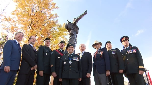 Honorary Colonel David Lloyd Hart, middle, stands among other military members and supporters at the unveiling of a monument honouring soldiers with PTSD in Kirkland.