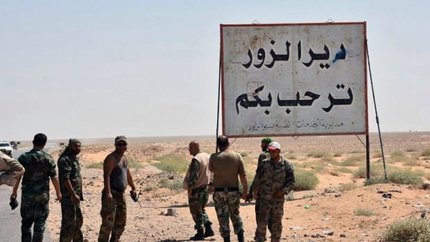 Syrian troops and pro-government gunmen stand next to a placard in Arabic that reads, 'Deir el-Zour welcomes you,' in the eastern city of Deir el-Zour, Syria on Sept. 3, 2017.