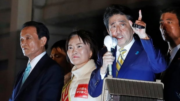 Japan's Prime Minister Shinzo Abe, leader of the Liberal Democratic Party, and Japan's Deputy Prime Minister Taro Aso, left, attend an election campaign rally in Tokyo on Saturday.