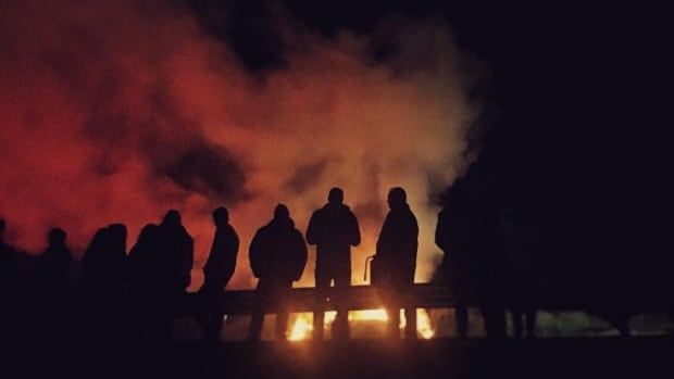 A crowd of onlookers watch as the fire on Citadel Hill burns.