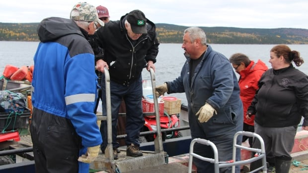 Sam Penney, 89, is helped off the ferry. Like most William's Harbour residents, he is 'getting up in age.'