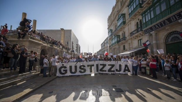 A banner reading 'justice' opens a rally in Malta to honour slain anti-corruption reporter Daphne Caruana Galizia in the capital city Valletta on Sunday.