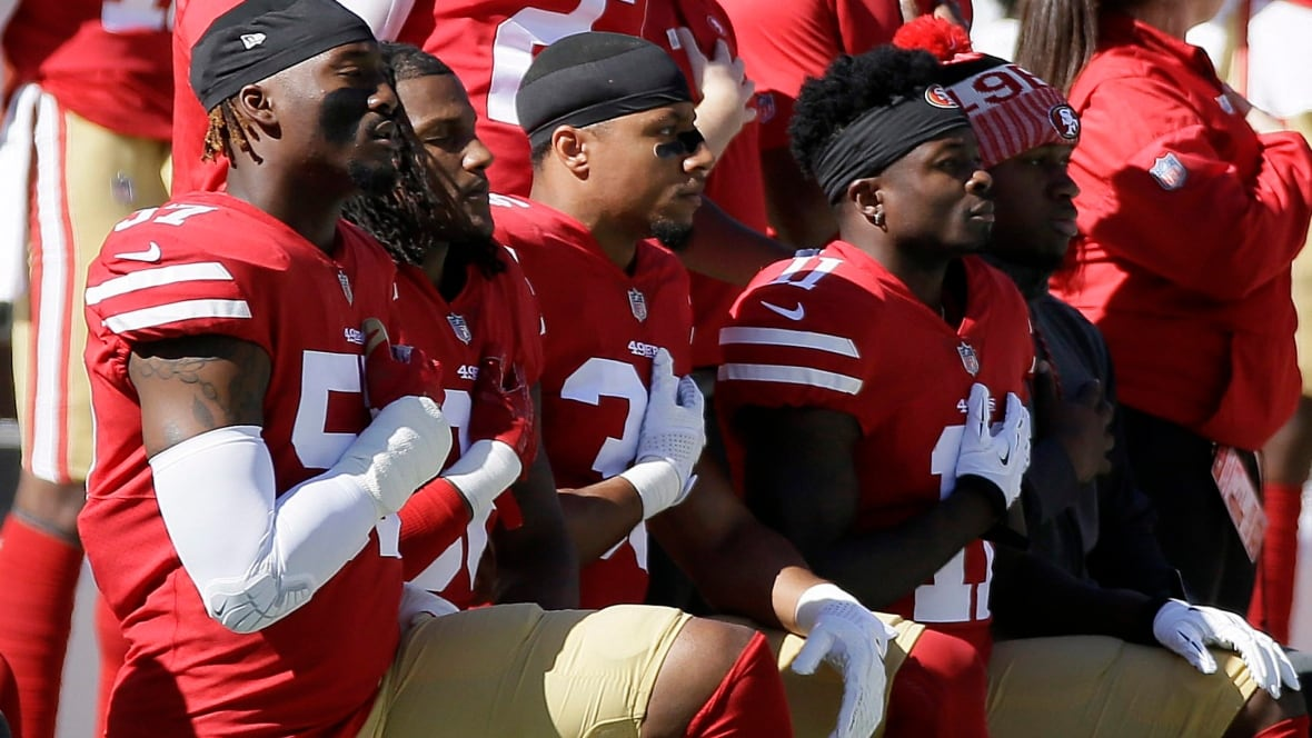 About 2 dozen NFL players protest during anthem