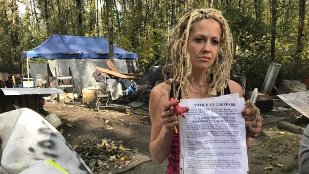 A resident of a homeless camp in Chilliwack holds up a notice of trespass. The group of people living there in tents have been ordered to leave by Monday at noon.