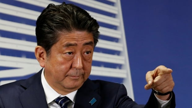Shinzo Abe attends a news conference at his party's headquarters in Tokyo on Monday after winning re-election as prime minister.