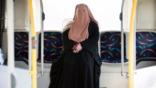 Warda Naili, a Muslim woman, poses for a photograph on a city bus in Montreal on Saturday. Quebec's new law on religious neutrality requires people to uncover their face to access public services, though how that will be enforced remains unclear.