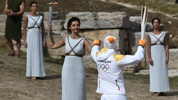An actor portraying the high priestess, left, hands the Olympic flame to Greek cross-country skier Apostolos Angelis to begin the torch relay for the 2018 Winter Games.
