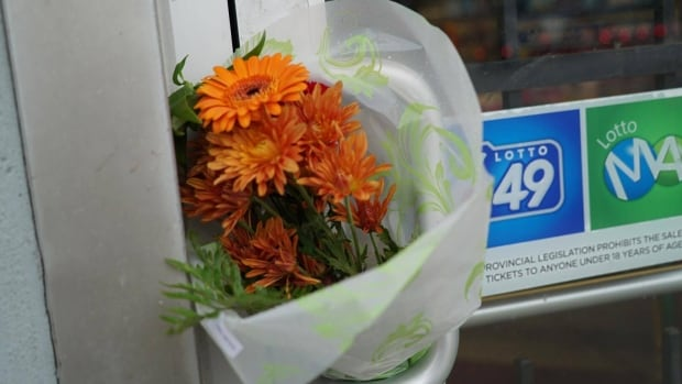 A bouquet of flowers was tucked away between the handle of a convenient store on Horton St. in London, the day after the store's owner was badly beaten.