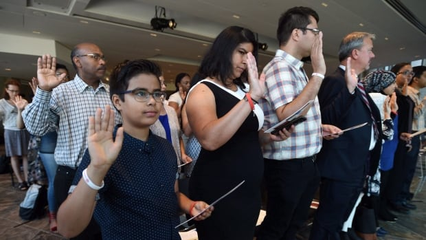 A group of new Canadians takes the citizenship oath during a ceremony at the National Arts Centre in Ottawa last month. Census figures released Wednesday show Canada is getting more diverse.