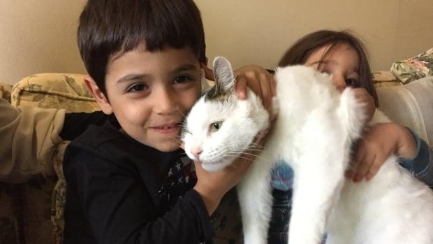 Abdul Razak, 5, cuddles Lonny while Ritaj, 4, looks on in the background.