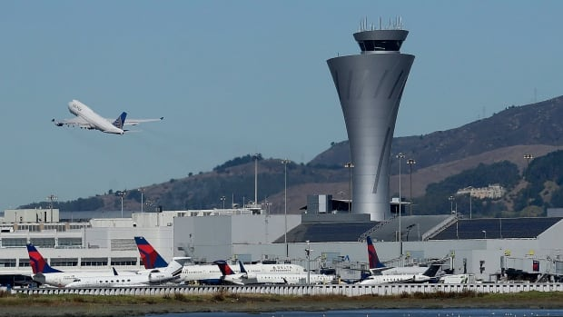 The air traffic control tower is in sight as a plane takes off from San Francisco International Airport. The Federal Aviation Authority is investigating why an Air Canada plane ignored repeated orders by an air traffic controller at the airport to abort a landing on Sunday.