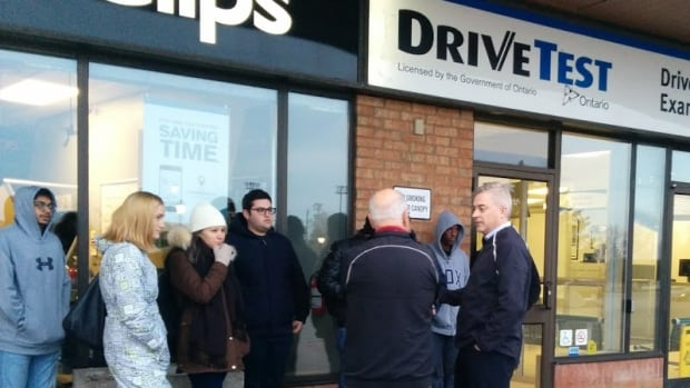 Kitchener-Conestoga MPP and PC transportation critic Michael Harris talks to people waiting outside the Drive Test office in Kitchener Friday morning. At least 30 people were lined up before the office opened.