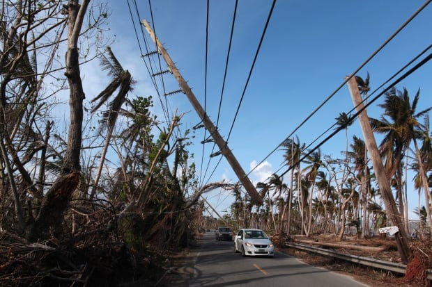 PUERTO RICO Cars drive under a partially collapsed utility pole