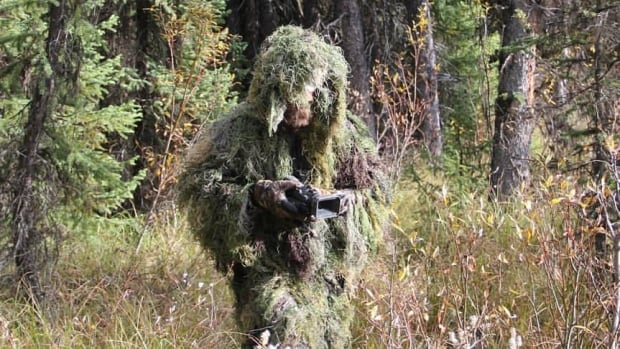 Todd Standing tracking Sasquatch in a custom camouflage ghillie suit.