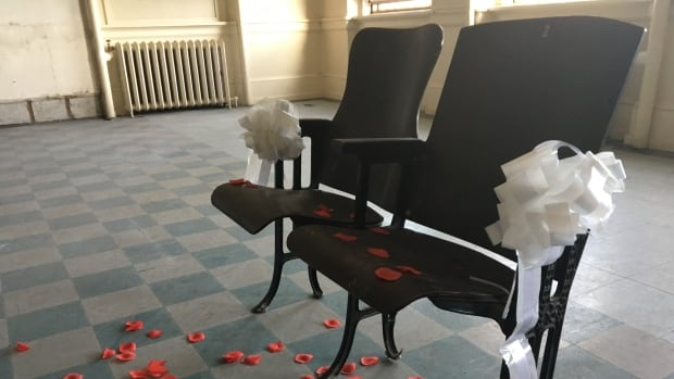 The former school's 100-year-old auditorium seats are available for purchase. On the weekend, the non-profit group decorated a pair to celebrate alumnae who got engaged in a classroom.