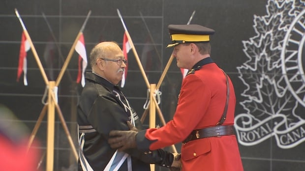 Keptin Donald Julien and RCMP Cmdr. Brian Brennan shake hands at the eagle feather ceremonial event on Monday in Dartmouth, N.S.