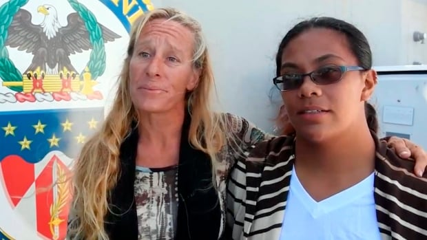 Jennifer Appel, left, and Tasha Fuiava, who with their dogs were rescued after several months at sea while trying to sail from Hawaii to Tahiti, are interviewed aboard the USS Ashland in the South Pacific Ocean.  Parts of their story have been called into question, including the tropical storm the two say they encountered on their first night at sea in May.