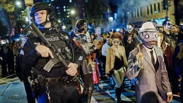 Heavily armed police watched as revellers marched during the Greenwich Village Halloween Parade on Tuesday in New York. New York City's always-surreal Halloween parade marched hours after a truck attack killed several people on a busy city bike path.