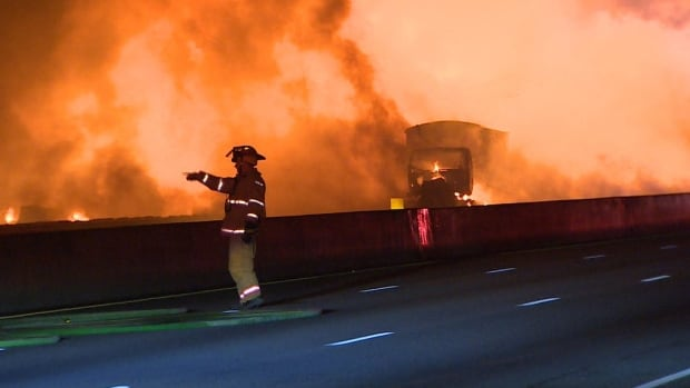 A fireman attends the scene of Tuesday's deadly crash on Highway 400, near Toronto. The cause of the crash is under investigation, but police say distracted driving appears to have been at least part of the problem.