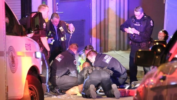 Emergency personnel work on a stabbing victim who has since died.