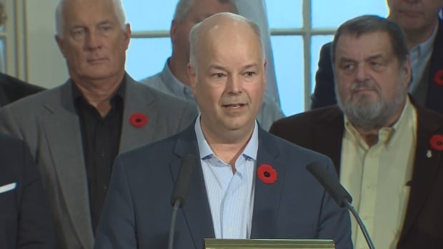 Jamie Baillie stood with PC MLAs as he said he was stepping down as party leader.