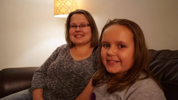 Veronica Van Buel, left, sits next to daughter Emily Van Buel, 9, right, who found a needle in a chocolate bar after she told her best friend to check her candy.