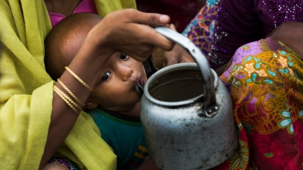Tears roll down the cheeks of a child while drinking water from a kettle, as Rohingya Muslims who have fled persecution in Myanmar wait along the border for permission to move further towards refugee camps near Palong Khali, Bangladesh, Thursday, Nov. 2, 2017.