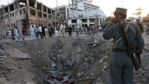 Security forces stand next to a crater created by massive explosion in front of the German Embassy in Kabul, Afghanistan, in May. The suicide truck bomb hit a highly secure diplomatic area of Kabul, killing scores of people and wounding hundreds more.
