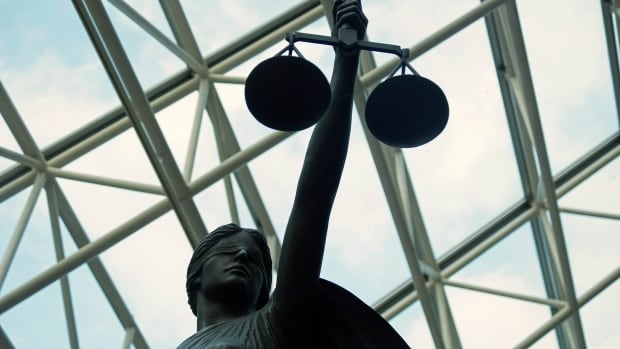 A statue of Lady Justice, blindfolded and holding balanced scales,  at Vancouver's Supreme Court.