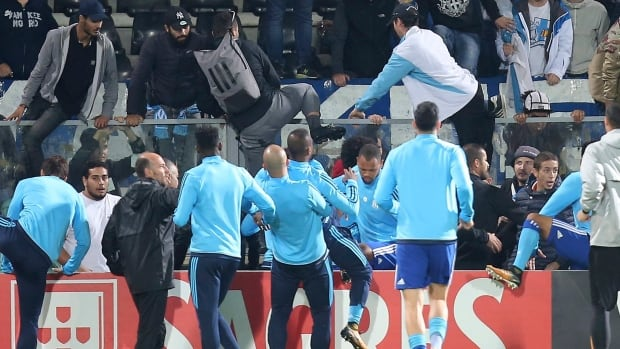 Marseille's Patrice Evra, centre, back to camera, is dragged away by his teammates during a scuffle with Marseille supporters who trespassed into the field before the Europa League group I soccer match between Vitoria SC and Olympique de Marseillein Guimaraes, Portugal, on Thursday.