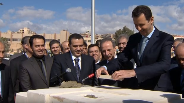 Syrian President Bashar al-Assad lays the first brick as part of an inaugural ceremony for a southern Damascus redevelopment project.