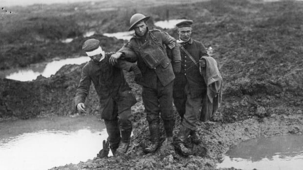 German prisoners help a wounded Canadian soldier navigate through the shellholes and mud. Many wounded drowned on the battlefield, accounting for the battle's large number of missing.