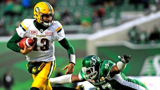 Edmonton Eskimos quarterback Mike Reilly runs the ball against Saskatchewan Roughriders' Rakim Cox.