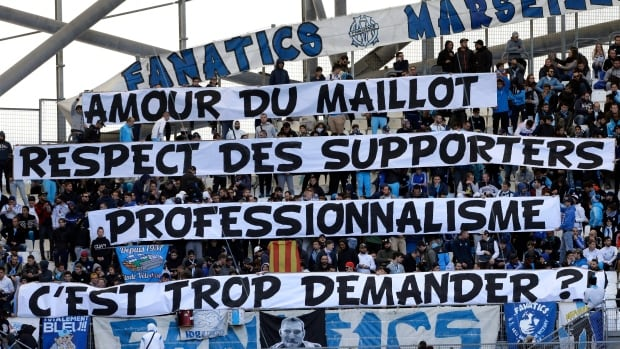 "Marseille supporters display banners reading ""Love of the jersey, respect for supporters, professionalism, is it too much to ask?"", prior to a match between Marseille and Caen, at the Velodrome stadium, in Marseille, southern France on Sunday. Fans were reacting to Marseille's Patrice Evra kicking the head of a supporter before a match against Vitoria SC Guimaraes earlier this week."