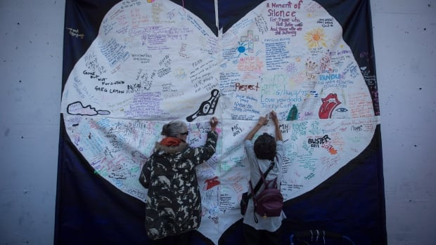 Women write messages on a banner during a memorial service to remember those who have died in the province as a result of the drug overdose crisis, on International Overdose Awareness Day Aug. 31, 2017 in the Downtown Eastside of Vancouver.
