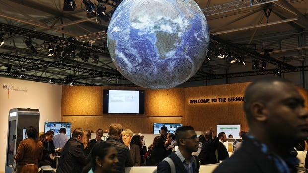 Delegates and visitors walk inside the German pavilion at the World Climate Conference in Bonn, Germany, Monday, Nov. 6, 2017. The U.N. weather agency says that 2017 is slated to be one of the top three hottest years on record.