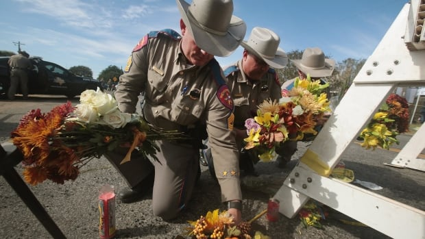 Police move flowers placed at a barricade near the First Baptist Church in Sutherland Springs, Texas. Twenty-six people were shot dead as they attended a church service in the small community on Sunday.