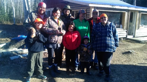 Maggie Etapp, in the green sweater, and her husband Simon Etapp, pose with their family outside their cabin. Both Maggie and Simon are living with diabetes and have their stories included in the collection.
