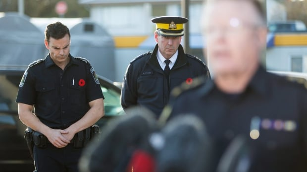 Police officers bow their heads while Abbotsford police Chief Bob Rich announces Const. John Davidson has died in hospital after being shot near Mt. Lehman Road and the Fraser Highway on Monday.