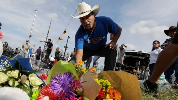 Rene Moreno drops off flowers at a makeshift memorial at the scene of a shooting at the First Baptist Church of Sutherland Springs, Texas. A man opened fire inside the church in the small South Texas community on Sunday.