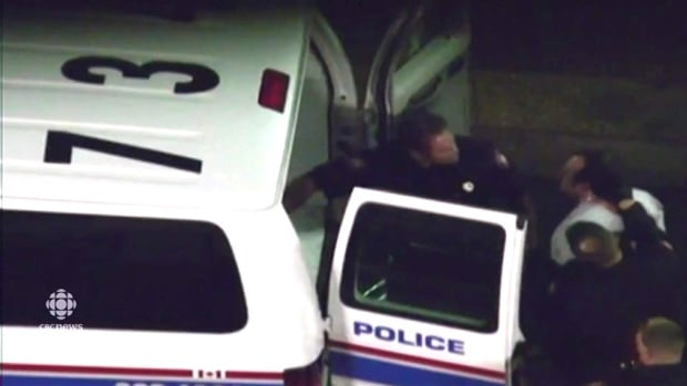 A screenshot of a video showing the arrest of Jason Arkinstall.