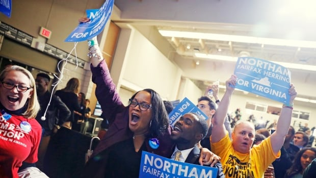 """Supporters of Democrat Ralph Northam celebrate as results start to come in at Northam's election night rally on the campus of George Mason University in Fairfax, Va. The night was a """"best-case scenario"""" for Democrats, one supporter said."""