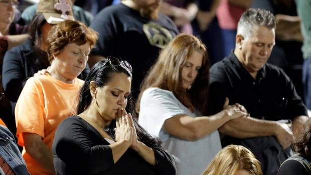 Attendees pray during a vigil for the First Baptist Church shooting victims Tuesday in La Vernia, Texas. FBI say they have been unable to access data from the cell phone of the shooter.