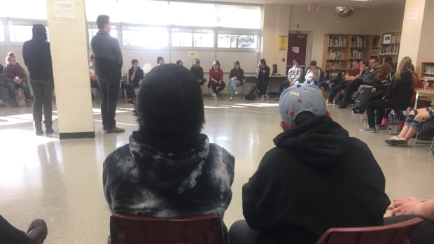 Students at Hammarskjold High School in Thunder Bay, Ont., gather in the library to hear Devin Peterson and Pamela Angees (standing) talk about reconciliation and treaties.