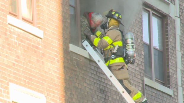 A firefighter helps a man in a smoke-filled apartment near the corner of Ouellette Avenue and Ellis Street W. on Nov. 8.
