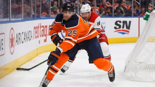 Edmonton Oilers' Darnell Nurse (25) carries the puck with Carolina Hurricanes' Justin Williams (14) in pursuit during an NHL game in Edmonton on Oct. 17, 2017.