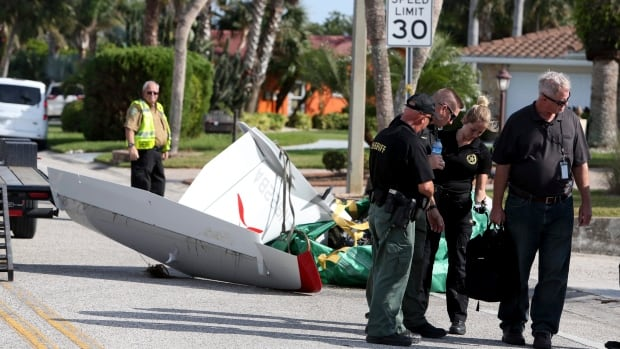 The tail section of Roy Halladay's ICON A5 ultralight plane lies on a roadway near a boat ramp in the Gulf Harbors neighborhood of New Port Richey, Fla., on Wednesday as investigators search for answers as to why it crashed into the Gulf of Mexico, killing the former Blue Jays pitcher.